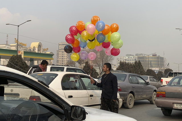 An Afghan balloon vendor looks for customers on a road in Kabul, Afghanistan, Monday, December 21, 2020. (Photo by Rahmat Gul/AP Photo)