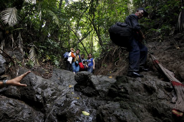 Cuban migrants look down as they cross the border from Colombia through the jungle into La Miel, in the province of Guna Yala, Panama November 29, 2015. (Photo by Carlos Jasso/Reuters)