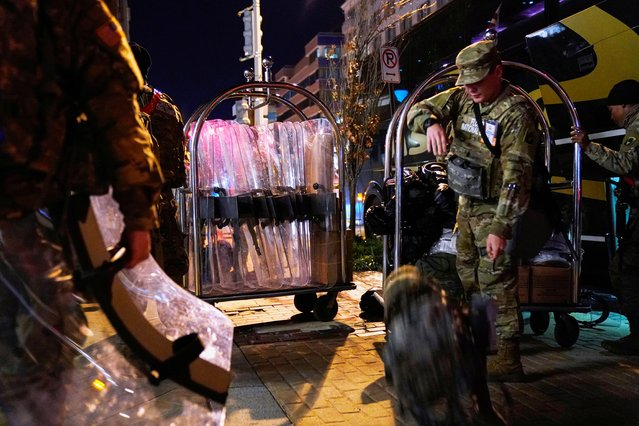 National Guard personnel wheel riot shields and baggage in hotel luggage carriers after checking out of their hotel in downtown Washington DC, U.S., January 20, 2021. (Photo by Erin Scott/Reuters)