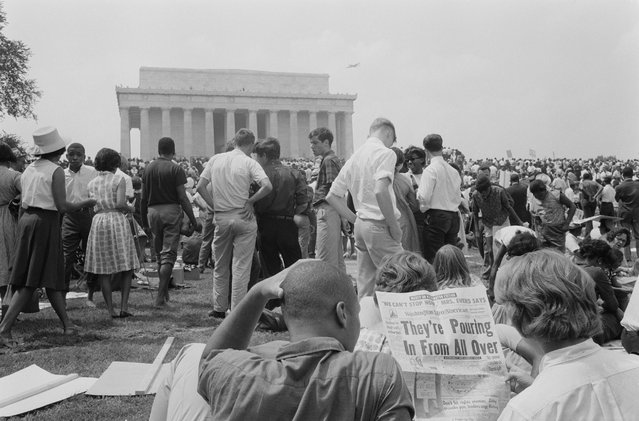 "A crowd of on the grounds of the Lincoln Memorial with two men in the foreground reading a newspaper with the headline ""They're Pouring In From All Over"" during the civil rights march on Washington D.C., August 28, 1963. (Photo by Reuters/Library of Congress)"