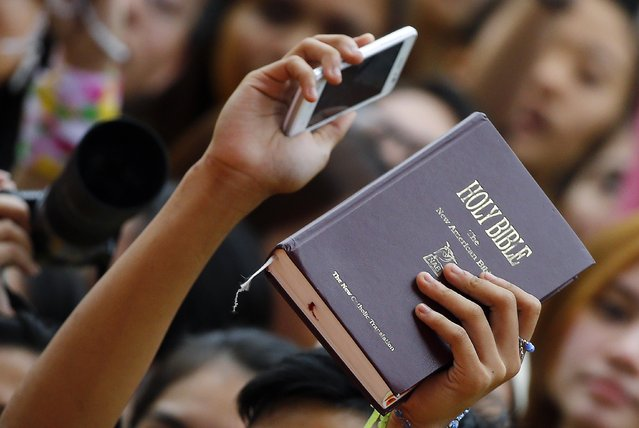 A girl holds a bible as Pope Francis arrives for a meeting with young people at Manila university, January 18, 2015. (Photo by Stefano Rellandini/Reuters)