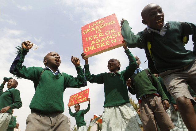 Students from Langata primary school hold placards as they protest against a perimeter wall illegally erected by a private developer around their school playground in Kenya's capital Nairobi, January 19, 2015. (Photo by Thomas Mukoya/Reuters)