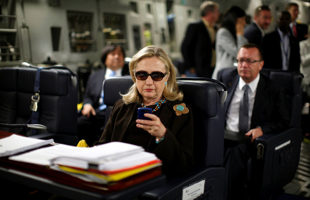 U.S. Secretary of State Hillary Clinton checks her PDA upon her departure in a military C-17 plane from Malta bound for Tripoli,  Libya October 18, 2011. (Photo by Kevin Lamarque/Reuters)
