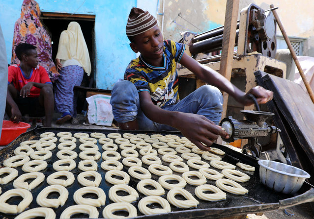 A Somali man prepares traditional cakes and biscuits inside a bakery ahead of the upcoming Eid al-Fitr holiday, marking the end of the Muslim holy month of Ramadan, in Mogadishu, Somalia June 13, 2018. (Photo by Feisal Omar/Reuters)