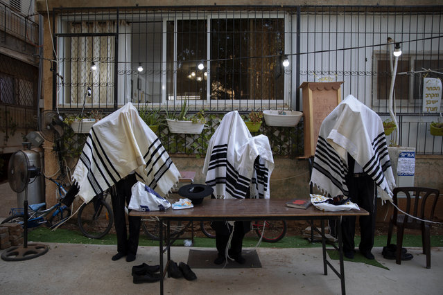 Ultra-Orthodox Jews pray covered in prayer shawls in divided sections which allow a maximum of twenty worshipers, next to their house as synagogues are closed following government measures to help stop the spread of the coronavirus, in Bnei Brak, Israel, Sunday, October 18, 2020. (Photo by Oded Balilty/AP Photo)