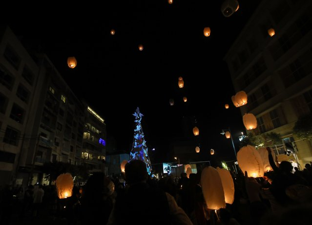 Lebanese launch lanterns in Beirut's Gemmayzeh neighbourhood on December 20, 2020, during the lighting of a Christmas tree in memory of the victims of the devastating port blast in that took place in the capital's port in August. (Photo by Anwar Amro/AFP Photo)