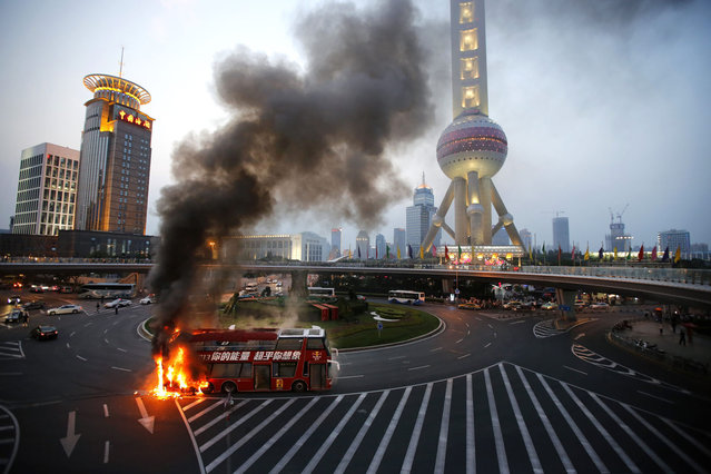 A double-decker tourism bus is seen on fire in from of the Oriental Pearl Tower in the Pudong financial district of Shanghai July 8, 2013. Passengers were seen walking away from the bus which burst into flames during rush hour at one of the busiest intersections in the city. (Photo by Carlos Barria/Reuters)