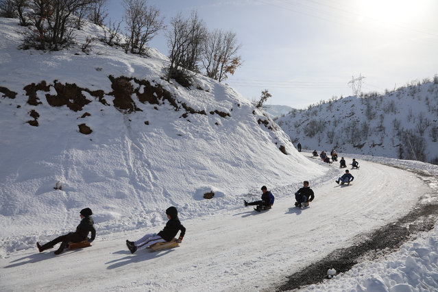 Children slide downhill with sledges after snowfall at Elmali village in Bingol province of Turkey on January 27, 2021. (Photo by Aydin Arik/Anadolu Agency via Getty Images)