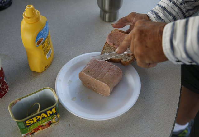 Resident Stanley Smith, 60, from Alabama, cuts spam for a meal at Camp Hope in Las Cruces, New Mexico October 5, 2015. (Photo by Shannon Stapleton/Reuters)