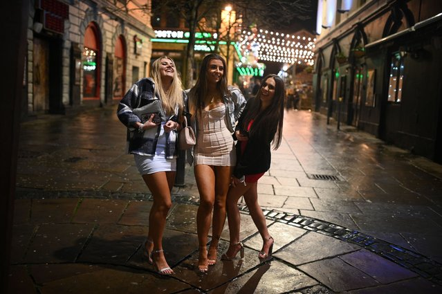 Revellers enjoy a night out in central Liverpool, northwest England, on December 30, 2020 before hightened Tier 3 restrictions closing hospitality venues, and bars indoor and outdoor socialising between households are imposed in the city amid surging cases of the novel coronavirus. Tighter coronavirus restrictions will be extended across England from on December 30 the British government announced, with a new Covid-19 variant blamed for a rapid surge in cases. Liverpool enters Tier 3, which closes hospitality venues, and bars indoor and outdoor socialising between households with the highest Tier 4 rules, which require all non-essential shops, hairdressers as well as leisure and entertainment venues to close, will now apply to more than 44 million people. (Photo by Oli Scarff/AFP Photo)