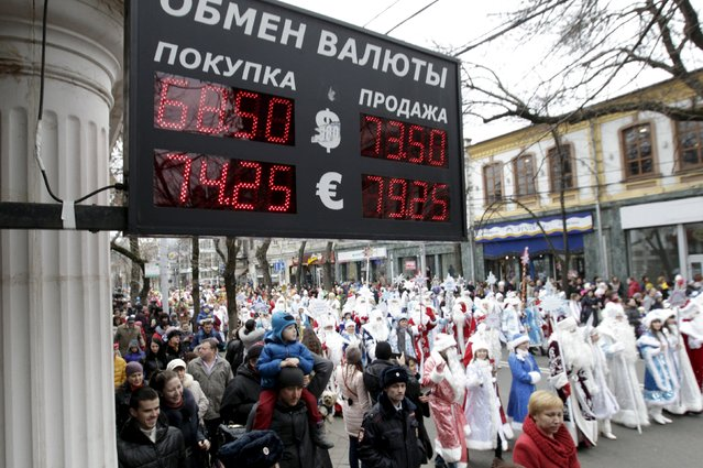 People, dressed as Ded Moroz, his granddaughter Snegurochka and other characters, walk during a festive pre-holiday procession, with a board showing currency exchange rates seen in the foreground, in Krasnodar, southern Russia, December 19, 2015. (Photo by Eduard Korniyenko/Reuters)