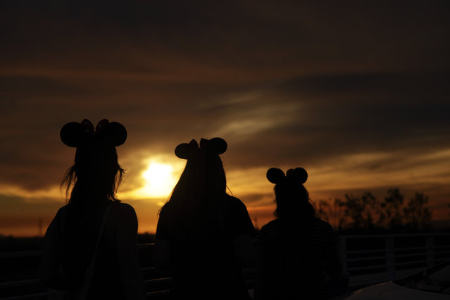 Wearing Minnie Mouse headbands, Chrissy Mut, from left, Megan Greenhouse and Nicky Mut, all of Sacramento, Calif., are silhouetted against the sunset as they walk toward their car on the parking structure of Disneyland, Thursday, January 22, 2015, in Anaheim, Calif. A major measles outbreak traced to Disneyland has brought criticism down on the small but vocal movement among parents to opt out of vaccinations for their children. (Photo by Jae C. Hong/AP Photo)