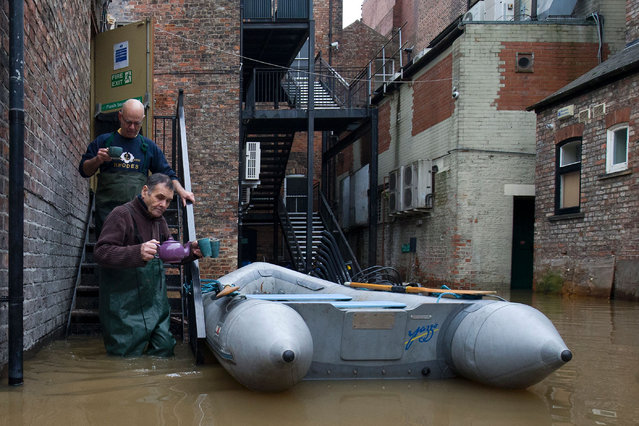 Workers from a taxi firm leave via the rear exit of a neighbouring wine bar with a teapot and three cups of tea, through the floodwaters from the rivers Foss and Ouse, after they burst their banks in York, northern England, on December 28, 2015. British Prime Minister David Cameron visited the flood-hit historic city of York on Monday as cities, towns and villages across northern England battled to get back on their feet following devastating storms. (Photo by Justin Tallis/AFP Photo)