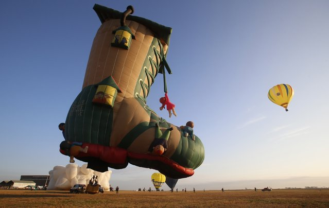 The Old Lady and the Shoe hot air balloon prepare to take off during the Philippine International Hot Air Balloon Fiesta at Clark Freeport Zone in Pampanga province, north of Manila February 12, 2015. (Photo by Erik De Castro/Reuters)
