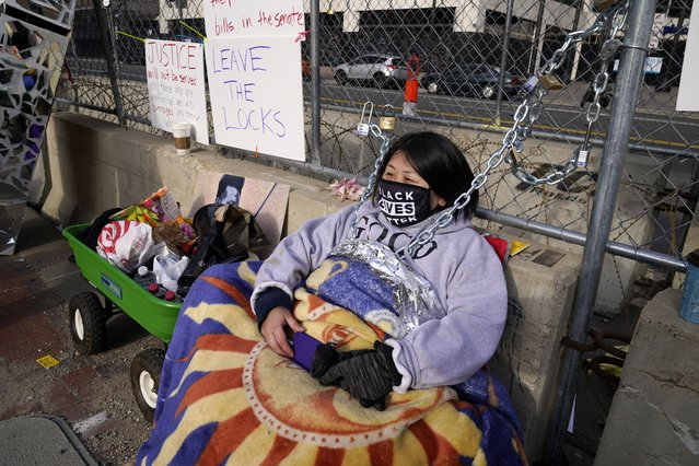 Kia Hirt sits with a chain attached to a fence while protesting outside the Hennepin County Government Center, Tuesday, March 30, 2021, in Minneapolis where the trial for former Minneapolis police officer Derek Chauvin continues. Chauvin is charged with murder in the death of George Floyd during an arrest last May in Minneapolis. (Photo by Jim Mone/AP Photo)