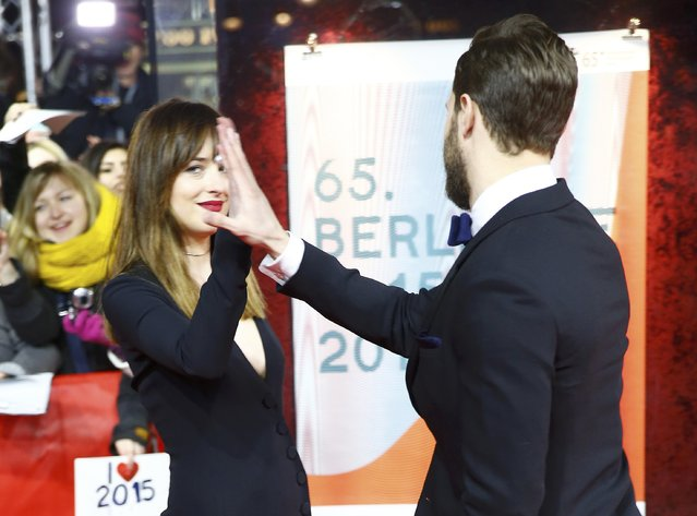"Actors Dakota Johnson and Jamie Dornan (R)  arrive for the screening of the movie ""Fifty Shades of Grey"" at the 65th Berlinale International Film Festival in Berlin February 11, 2015. (Photo by Hannibal Hanschke/Reuters)"
