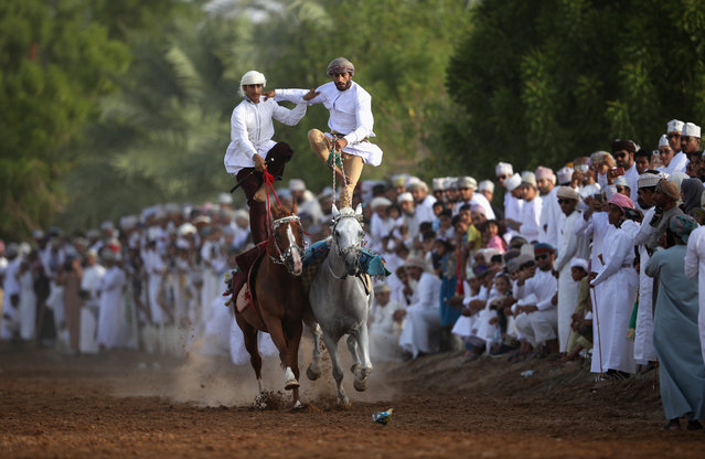 Omani horse riders take part in a traditional horse show on August 23, 2018 in Ibra, Oman.The purpose of the performance is to show the skills of the riders and the relationship they have with the horses. (Photo by Francois Nel/Getty Images)