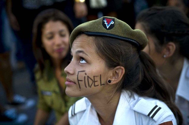 A cadet from the Interior Ministry with the word Fidel painted on her face attends a rally honoring the late Cuban leader at the Revolution Plaza in Havana, Cuba, Tuesday, November 29, 2016. Schools and government offices were closed Tuesday for a second day of homage to Fidel Castro, with the day ending in a rally on the wide plaza where the Cuban leader delivered fiery speeches to mammoth crowds in the years after he seized power.Fidel Castro passed away Friday Nov. 25. He was 90. (Photo by Ramon Espinosa/AP Photo)
