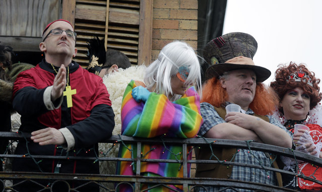 Revelers in costume watch from a balcony during the Society of Saine Anne parade on Mardi Gras in New Orleans, Tuesday, February 17, 2015. (Photo by Gerald Herbert/AP Photo)