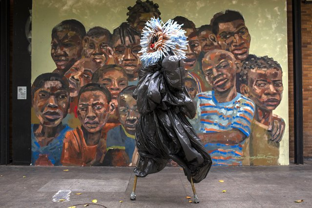 """A performing artist balances on stilts dressed in a costume representing ancestral spirits during a video recording of """"Giant Dreamers"""" outside the MAM or Museum of Modern Art (MAM) during the COVID-19 pandemic in Rio de Janeiro, Brazil, Tuesday, March 9, 2021. The show is funded by the government and features artists recreating the magic of Carnival. (Photo by Bruna Prado/AP Photo)"""