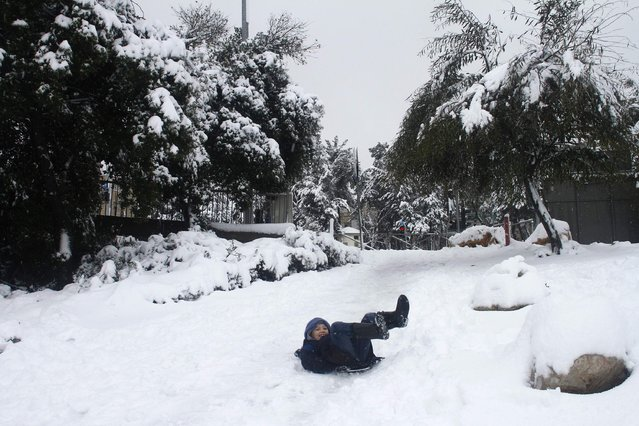 A boy uses a makeshift sled in a snow-covered park in Jerusalem February 20, 2015. (Photo by Sharon Perry/Reuters)