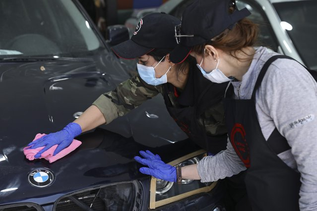 Female car detailer Maryam Roohani polishes a car as her trainee Farahnaz Deravi watches, at a detailing shop in Tehran, Iran, April 18, 2021. The auto industry remains male-dominated around the world, let alone in the tradition-bound Islamic Republic. Still Iranian women, especially in the cities, have made inroads over the years. (Photo by Vahid Salemi/AP Photo)