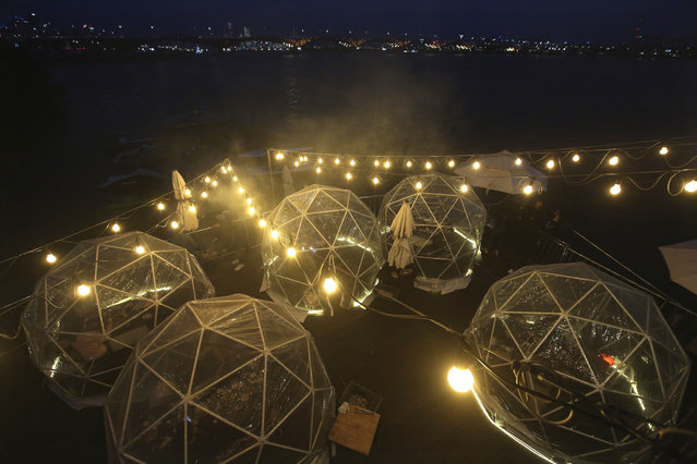 People enjoy outdoor dining at plastic bubbles, observing social distancing against the spread of the coronavirus at a restaurant near the Han River in Seoul, South Korea, Friday, April 9, 2021. (Photo by Ahn Young-joon/AP Photo)