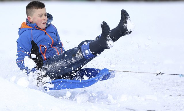 A boy on a sledge is towed in a Perthshire field  Scotland, Britain January 17, 2016. (Photo by Russell Cheyne/Reuters)