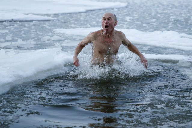 A man takes a dip in icy waters during celebrations for the Orthodox Epiphany on the Dnipro River in Kiev, Ukraine, January 19, 2016. (Photo by Valentyn Ogirenko/Reuters)