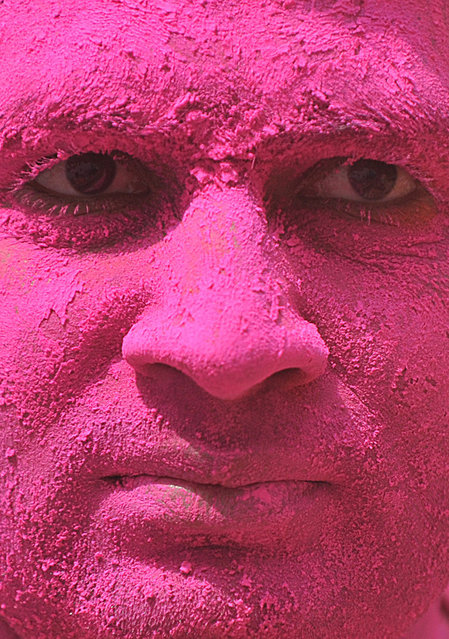 Indian reveller is covered with coloured powder during Holi celebrations in Hyderabad on March 6, 2015.  Holi, also called the Festival of Colours, is a popular Hindu spring festival observed in India at the end of the winter season on the last full moon day of the lunar month.  AFP PHOTO / Noah SEELAM        (NOAH SEELAM/AFP/Getty Images)