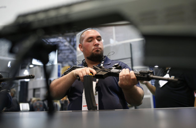 David Monteiro looks at a gun at the Barrett booth at the Shooting, Hunting and Outdoor Trade Show, Tuesday, January 19, 2016, in Las Vegas. (Photo by John Locher/AP Photo)