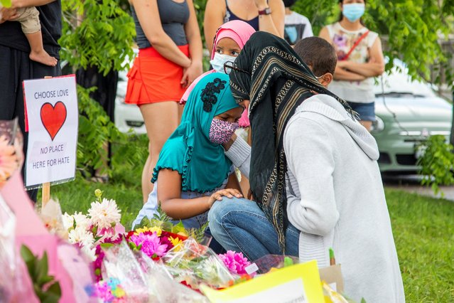 Kira Stephani speaks with her daughters Aisha Sayyed and Aliyah Sayyed at a makeshift memorial at the fatal crime scene where a man driving a pickup truck jumped the curb and ran over a Muslim family in what police say was a deliberately targeted anti-Islamic hate crime, in London, Ontario, Canada on June 8, 2021. The suspect does not have a criminal record, and is not known to be a member of a hate group, police said. He was arrested in a mall parking lot without incident while wearing a body-armor-type vest, police said. There is no evidence he had any accomplices. It was not immediately known if the suspect had hired a lawyer. (Photo by Carlos Osorio/Reuters)