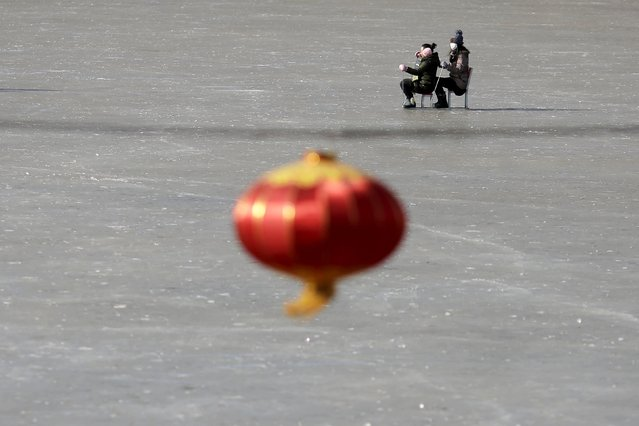 People move on improvised sleds on a frozen lake as citizens enjoy a sunny day despite sub-zero temperatures in Beijing, January 24, 2016. (Photo by Damir Sagolj/Reuters)