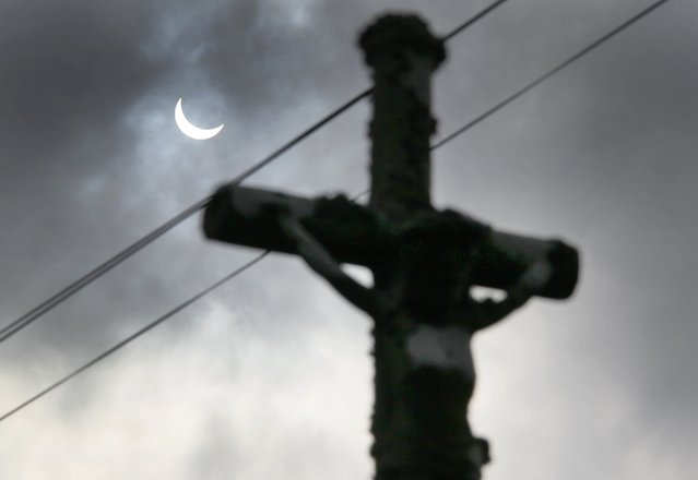 A partial eclipse of the sun is seen through clouds behind a roadside crucifix at Goulien, in Finistere, western France, March 20, 2015. (Photo by Mal Langsdon/Reuters)