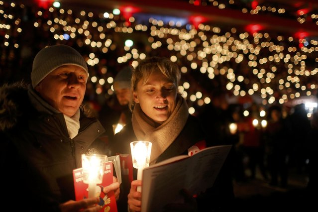 """People attend the """"Weihnachtssingen"""", a candle-lit carol concert with 28500 fans of the second-division club FC Union Berlin at the Alte Foersterei stadium in Berlin, Germany, December 23, 2016. (Photo by Hannibal Hanschke/Reuters)"""