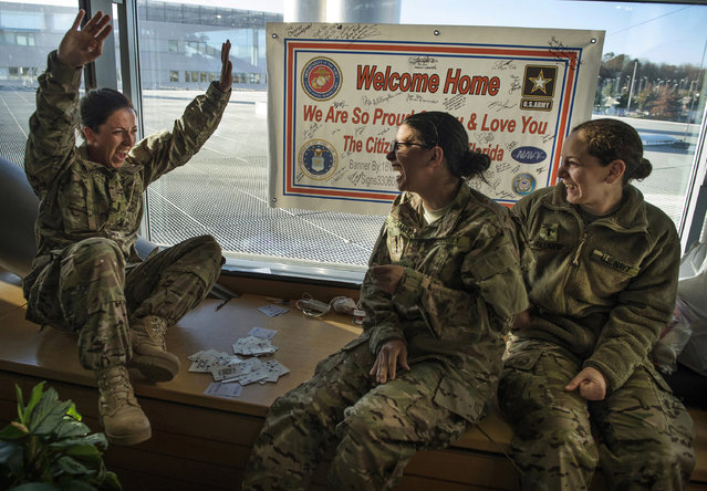 U.S. Navy Lieutenant Jaclyn Trosper celebrates winning a card game, February 17, 2014. The military members found ways to occupy time while transitioning to a deployment in Afghanistan. (Photo by Staff Sgt. Vernon Young/U.S. Air Force)