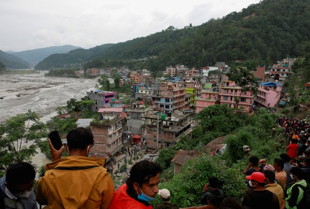 People gather on higher ground as flood water from the swollen Melamchi river enters the village in Sindhupalchok, Nepal, June 16, 2021. (Photo by Navesh Chitrakar/Reuters)