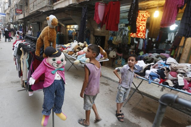 A boy looks at stuffed toys displayed amid clothes for sale ahead of the Muslim festival of Eid-al-Adha in Aleppo, Syria September 23, 2015. (Photo by Hamid Khatib/Reuters)
