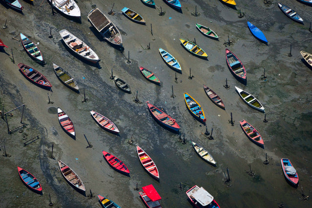 Small boats sit on the shore of Guanabara Bay in the suburb of Sao Goncalo, across the bay from Rio de Janeiro, Brazil, Tuesday, November 19, 2013. The bay was home to a thriving artisanal fishing industry and popular palm-lined beaches as recently as the late-1970s, but has become a watery dump for waste from shipyards and two commercial ports. Rio de Janeiro will host the 2016 Olympic Games. (Photo by Felipe Dana/AP Photo)