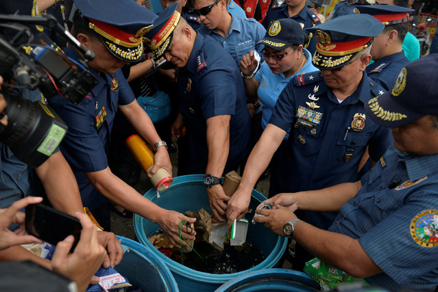 Philippine National Police (PNP) Director General Ronald Dela Rosa (C), along with other police officials, dunks confiscated illegal firecrackers into a tub of water to render them unusable, during an inspection of firecracker shops ahead of new year celebrations in Bocaue, Bulacan province, north of Manila, Philippines, December 29, 2016. (Photo by Ezra Acayan/Reuters)