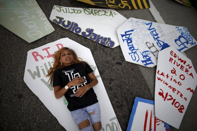 """People stage a """"die-in"""" in the middle of the road after carrying coffins during a march to commemorate the more than 617 people they say have been killed by law enforcement in LA County since 2000, in Los Angeles, California April 7, 2015. (Photo by Lucy Nicholson/Reuters)"""