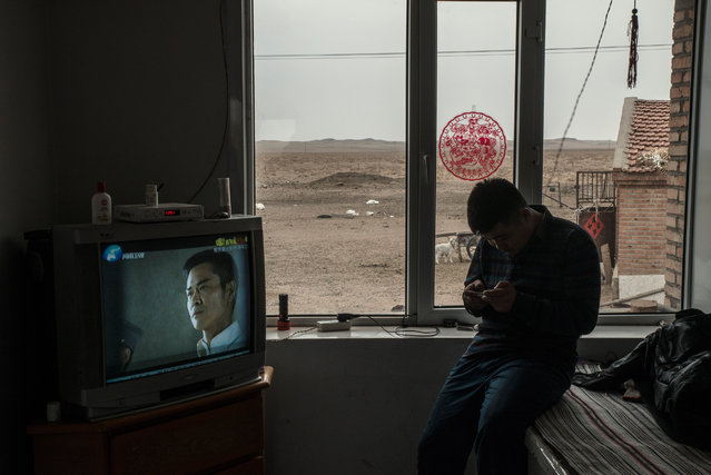 A herder checking his phone at home near an army training camp. The eviction of herders from their grassland for the extension the training base has led to protests. (Photo by Gilles Sabrie/The Washington Post)