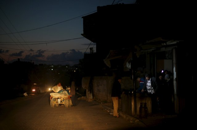 A vendor fries Falafel as Palestinians wait to buy during a power cut at a street lit by passing cars in the northern Gaza Strip, February 10, 2016. (Photo by Mohammed Salem/Reuters)