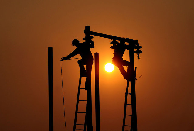 Indian electricians adjust electric cables set up temporarily on the banks of the river Ganga in preparation for the annual Hindu religious fair of Magh Mela in Allahabad, on December 16, 2013. (Photo by Sanjay Kanojia/AFP Photo)