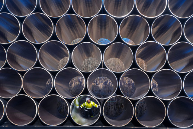 A worker inspects stacks of pipes weighing several tons each which will be used for the construction of the Nord Stream gas pipeline in the Sassnitz-Mukran harbour in northeastern Germany, 06 December 2016. The first sections of the 1,200 kilometer pipeline were delivered in late October 2016. Around 2,000 of a total 90,000 steal pipe components are currently being stored on the island of Ruegen. According to the Gazprom subsidiary Nord Stream 2 AG, the assembly works will begin in mid-2017. So far the political controversial pipeline, which will have a total capacity of some 55 billion cubic meters, has not recieved building permission. (Photo by Jens Buettner/EPA)