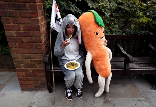 An Extinction Rebellion climate activist eats while sitting on a bench dressed as a bunny and holds a plush toy carrot during a protest in London, Britain on August 28, 2021. (Photo by Peter Nicholls/Reuters)