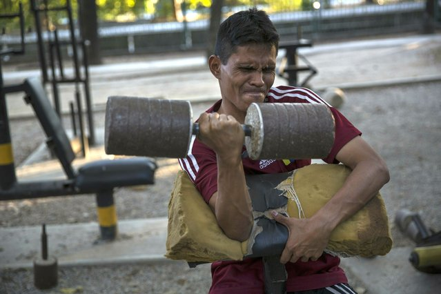 "A man lift weights in a makeshift gym at Los Caobos public park in Caracas, Venezuela, Saturday, January 26, 2019. The United States urged all nations Saturday to support Venezuelan opposition leader Juan Guaido while Russia accused the Trump administration of attempting ""to engineer a coup d'etat"" against President Nicolas Maduro, a reflection of the world's deep divisions over the crisis in the embattled Latin American country. (Photo by Rodrigo Abd/AP Photo)"