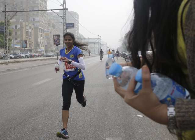 An Egyptian volunteer holds water bottles for  passing runners participating in Cairo's  annual Half Marathon in the Heliopolis district in Cairo, Egypt, Friday, April 17, 2015. The streets are jammed at nearly all hours with smoke-belching microbuses, manic taxis, speeding motorbikes and the occasional donkey cart. The crumbling sidewalks are often worse – and yet despite all the obstacles, young Egyptians have launched several increasingly popular running clubs over the past two years. (Photo by Amr Nabil/AP Photo)