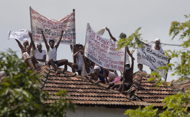 """Death-row inmates of Sri Lanka's Welikada prison protest holding banners from the roof of the prison in Colombo, Sri Lanka, Friday, June 25, 2021. About 150 death-row inmates in Sri Lanka began a hunger strike to demand their sentences be commuted, prison officials said, after the nation's president pardoned a former lawmaker who had been condemned for an election-related killing. Banners read """"Treat all inmates equally"""", """"Grant bail on appeal applications"""",  """"Minister! Stop bogus promises"""", """"Grant pardon to us like you did to terrorists and notorious politicians"""". (Photo by Eranga Jayawardena/AP Photo)"""