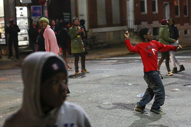 A child throws a rock at police as protesters gather for a rally to protest the death of Freddie Gray who died following an arrest in Baltimore, Maryland April 25, 2015. (Photo by Shannon Stapleton/Reuters)